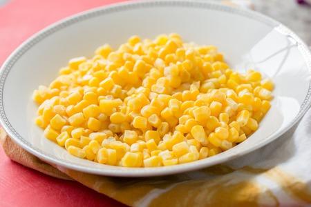 fresh sweet yellow corn kernels in white bowl Standard-Bild