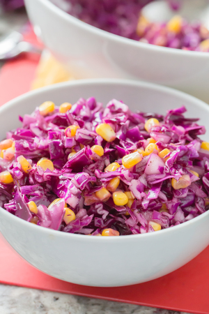 red cabbage and corn salad in white bowl