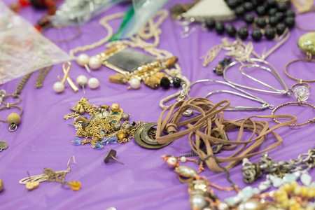 variety of homemade jewellery on purple table Imagens