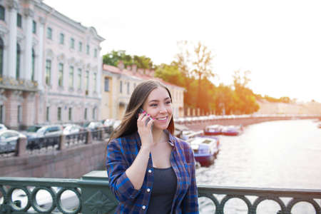 Young beautiful smiling hipster girl talking on mobile phone, standing outdoors near embankment river. Charming cheerful woman tourist having cell telephone conversation during walk outside in summer