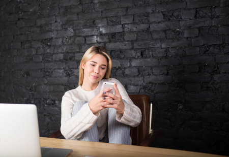 Young pretty woman student reading text message on mobile phone after work on laptop computer. Gorgeous blonde hipster girl having video call on cell telephone, siting in modern interior