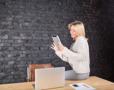 Smiling woman manager having video call on touch pad, sitting on a work table with laptop computer and paper documents. Female secretary using digital tablet, sitting against wall with copy space