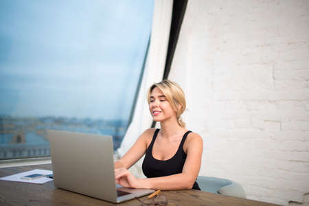 Happy woman financier working with important electronic documents on laptop computer, sitting in modern office near big window.Smiling female student keyboarding on portable net-book, learning on-line
