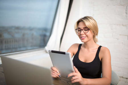 Smiling female student having video call on-line via touch pad, sitting in modern interior. Happy woman publication specialist reading on digital tablet good response about her work. Office worker Stock fotó