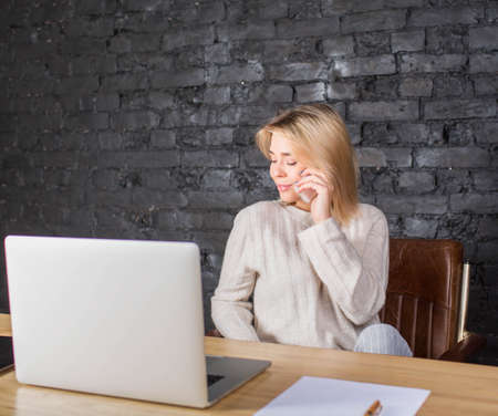 Beautiful businesswoman talking on mobile phone, sitting at the work table with laptop computer and contract. Confident female content manager or secretary having cell telephone conversation
