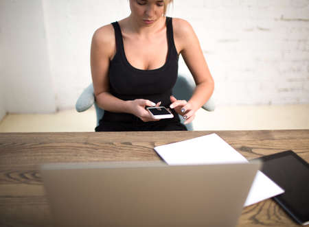 Hipster girl typing text on mobile phone, sitting at the wooden table with laptop computer, touch pad and paper documents. Female freelancer chatting on cell telephone during work day in co-working