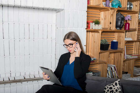 Woman content manager reading e-mail on touch pad and calling via mobile phone, sitting in modern office. Female executive director reading summary in internet and talking on cellphone with subordinate