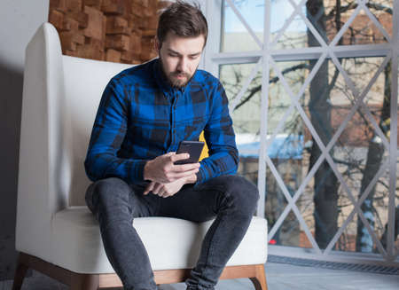 Young modern businessman reading text message on mobile phone, sitting in office near window with copy space. Bearded male web content writer reading information via cell telephone