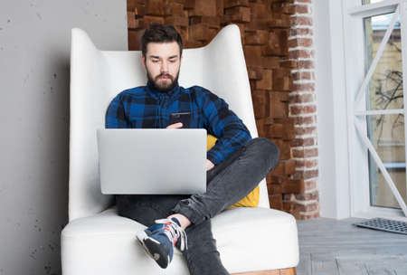Confident man dressed in stylish clothes successful project manager in network reading notification on mobile phone during work on laptop computer sitting in modern office space. Hipster guy chatting