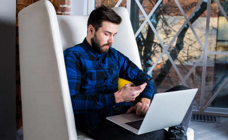 Bearded man site administrator and groups in social networks using mobile phone and laptop computer for work, sitting in modern office space. Confident male entrepreneur checking message on cellphone