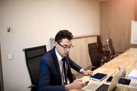 Successful business man reading text message on mobile phone while sitting at the table with laptop computer in office company. Male professional manager checking e-mail on cellphone during work day