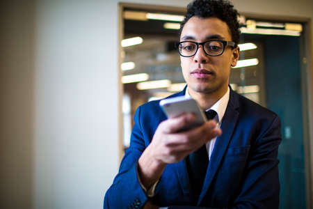 Serious man CEO in suit and glasses using applications on mobile phone standing in office near copy space. Thoughtful male leadership watching video in internet via smartphone. Online payment
