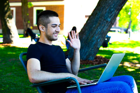 Cheerful hipster guy waving hand hello during online video call on laptop computer, resting in park during free time in weekend. Happy man freelancer having webcam conference via notebook device