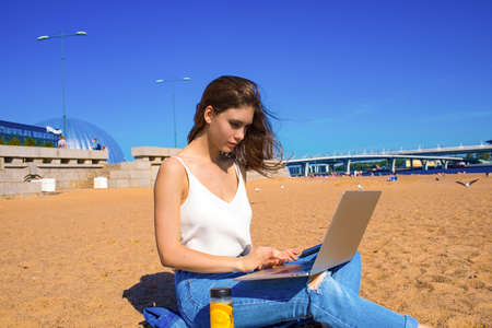 Young woman university student having online learning via laptop computer while sitting on the beach in sunny day. Female skilled writer keyboarding on notebook. Girl having distance work via netbook