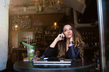Young woman with long beautiful hair talking via mobile phone during recreation time in coffee shop, sitting near copy space for promotional content. Female university student having smartphone call