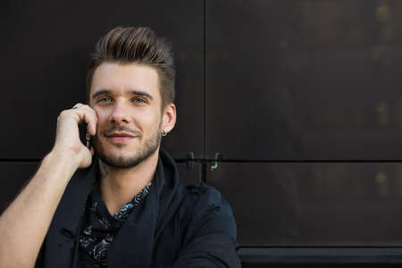 Handsome bearded man with good mood talking via cell telephone standing near wall with copy space for advertising text. Brutal stylish male having mobile phone conversation