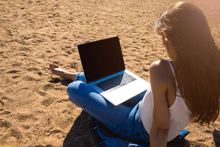 Woman watching movie on laptop computer with empty copy space screen background for advertising content while relaxing on beach in sunny summer day. Female skilled blogger reading article on netbook