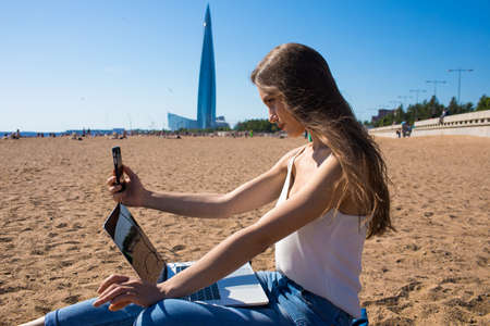 Charming woman making self portrait on front mobile phone camera while relaxing with laptop computer on the beach in sunny day. Female having video call via cellphone during distance work on notebook