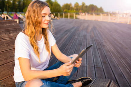 Female freelance social media content writer reading article on web site via touch pad while sitting outdoors in summer day. Woman university student reading electronic book on digital tablet