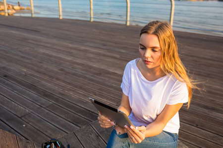 Gorgeous woman checking notification on touch pad while sitting outdoors near copy space for promotional content. Female blogger online banking via digital tablet during rest on sea quay in evening