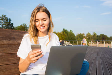 Smiling charming woman reading text message via mobile phone during distance work on laptop computer while sitting on bench in park in sunny summer day. Female writer using messenger on cellphone