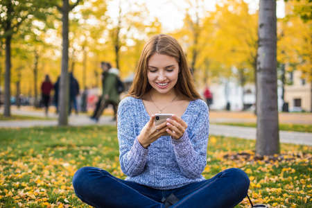 Happy smiling hipster girl watching funny video in social network via smartphone cellular while resting in autumn park during recreation time in vacation. Cheerful woman typing text in cellphone