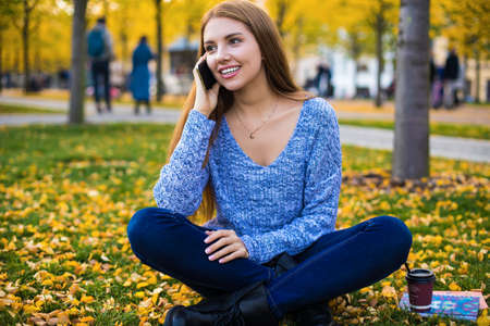 Young smiling woman university student with beautiful smile on the face talking via mobile phone while sitting in autumn park in warm day during recreation time. Female phoning via cellphone cellular