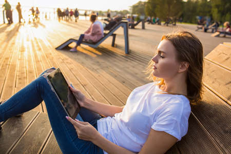 Young Caucasian woman blogger reading article on website via touch pad while relaxing outdoors in park in sunny summer evening. Female online shopping store via digital gadget leisure during time Imagens