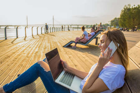 Young hipster girl talking via mobile phone during distance online training course on laptop computer while relaxing outdoors on sea embankment in sunny summer day. Fashionable woman phoning via pda
