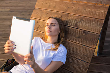 Young charming woman reading electronic book on portable touch pad while relaxing outdoors during summer recreation. Female watching video on digital gadget while sitting on wooden bench in park Imagens