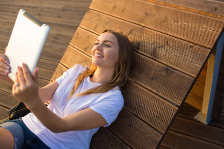 Happy smiling woman having online video conference via portable touch pad device while relaxing in park in sunny summer day. Lovely cheerful female online shopping store via digital gadget