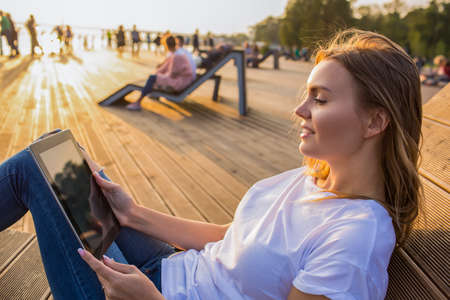Smiling woman online booking via portable touch pad while relaxing outdoors in sunny summer evening during recreation time in vacation. Female reading e-book via digital tablet during rest