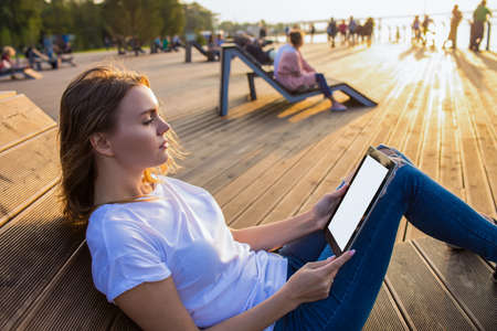 Attractive woman reading news in internet via modern touch pad with empty mock up copy space screen background for promotional content while sitting on bench in park in sunny summer evening.