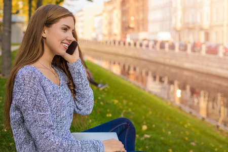 Young happy smiling fashionable woman talking via smartphone while enjoying good warm autumn day, sitting outdoors near quay river background with copy space for promotional content
