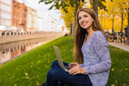 Smiling woman freelance content writer dreaming during work on laptop computer while sitting in park near embankment river background with copy space. Cheerful female having online learning via netbook