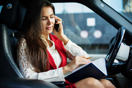 Busy woman skilled leadership talking with employee via mobile phone and reading information from textbook while sitting in luxury car during break at job. Cheerful female lawyer having smartphone call