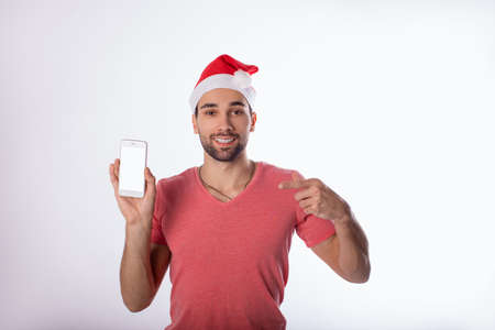 Portrait of a happy smiling man in red Canta Clause hat showing finder on smartphone with empty mockup copy space screen background for advertising text message, standing isolated in studio