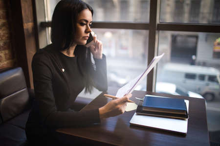 Confident woman proud entrepreneur reading contract and talking with partner via cell telephone, sitting in modern office interior. Prosperous female executive director reading paper documents