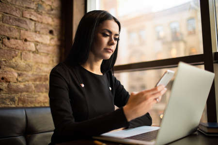 Serious woman experienced business plan writer received notifications on smartphone during online conference via laptop computer, sitting in restaurant.Proud female real estate analyst using cellphone