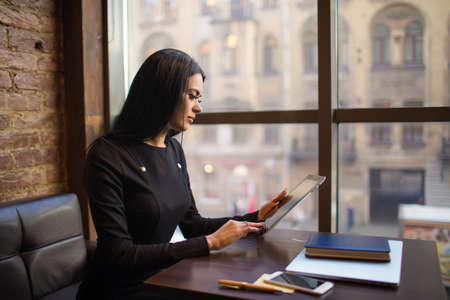 Prosperous woman skilled employer searching resume in internet via touch pad computer while siting at workplace with working tools. Fashionable female blogger posting article via digital gadget