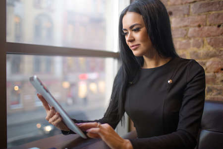 Woman successful government worker checking e-mail on portable touch pad computer, sitting in restaurant after work day. Confident female lawyer using application on digital tablet during rest in cafe