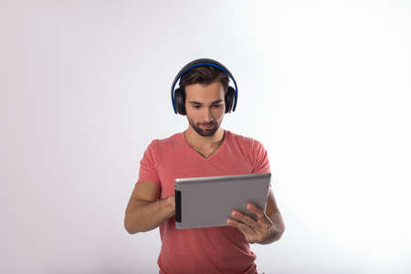 Young bearded hipster guy in stylish t-shirt listening to music via headphones while searching information in internet via portable touch pad while standing isolated in studio against wall