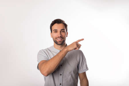Happy smiling bearded man office worker showing finder on copy space background for promotional content while standing isolated in studio