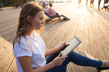 Woman skilled fashion blogger reading article on web site via touch pad while relaxing outdoors in park in sunny summer evening during vacation time. Hipster girl online payment via digital gadget Imagens
