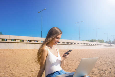 Pretty woman with beautiful smile on the face and long hair holding in hand mobile phone and watching online video while sitting on the knee with laptop computer on sea beach in sunny summer day