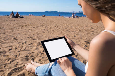 Female blogger using portable touch pad computer with empty mock up copy space screen background for promotional content. Hipster girl using digital gadget with blank monitor, relaxing near sea Imagens