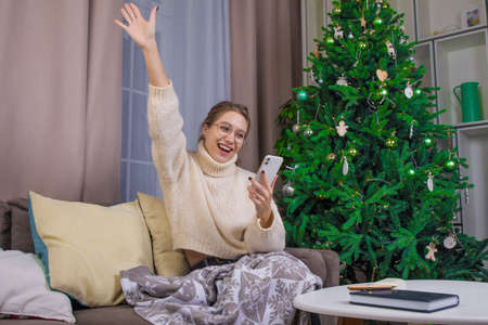 Happy successful woman with hand up celebrating victory while reading e-mail on mobile phone, relaxing on home near Christmas tree during winter holidays Stock fotó