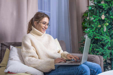 Joyful hipster girl checking e-mail via laptop computer while sitting in home near Christmas tree
