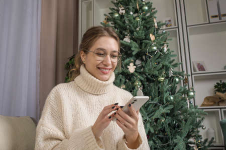 Happy smiling woman in stylish glasses using apps on mobile phone while sitting in home near Christmas tree during winter holidays