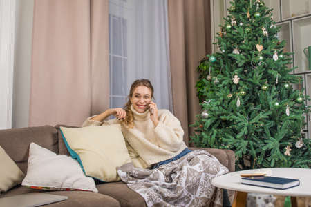 Happy smiling woman talking with friend via mobile phone while sitting in home near beautiful Christmas tree during quarantine